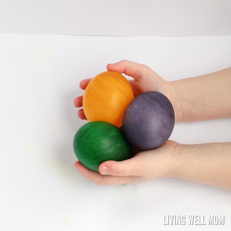 child holding 3 dyed rubber eggs (spring STEM activitiy)