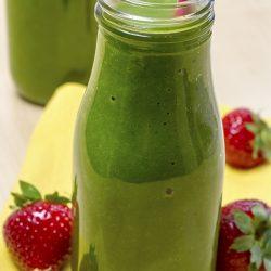 Healthy green juice smoothie in glass bottle sitting on yellow napkin with fresh strawberries.