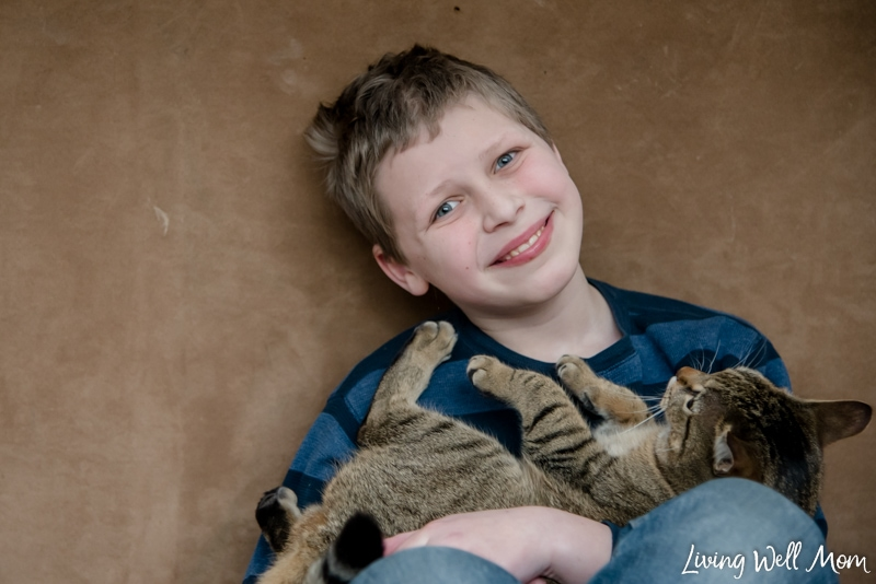 A young boy holding a cat