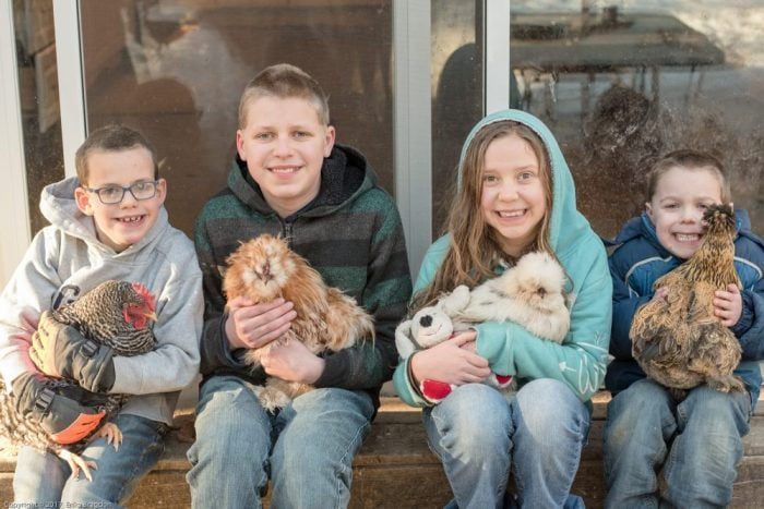 four kids holding chikens