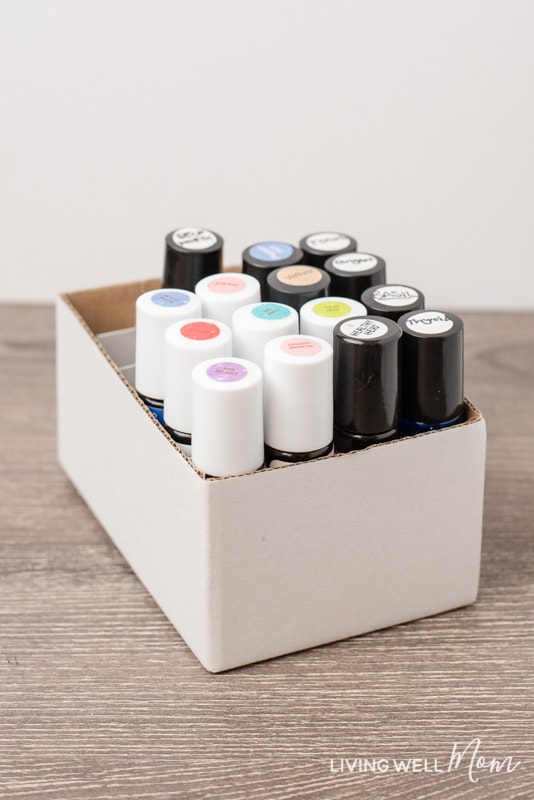 filled essential oil roller bottles with labels in a white cardboard box with dividers