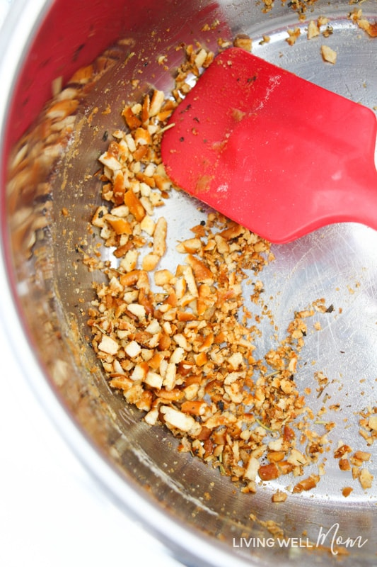 Pretzel crumbs in a pan being stirred with a red silicone spatula.