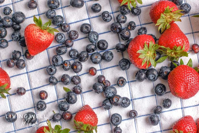 Berries on a dish towel air-drying after being soaked and rinsed.