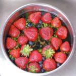 strawberries in blueberries soaking in homemade vegetable wash