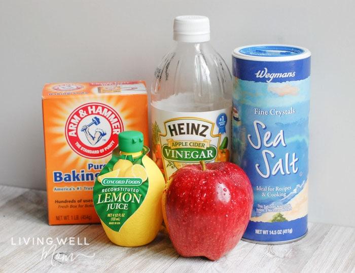 Produce wash ingredients - baking soda, vinegar, salt, and lemon juice next to an apple.