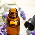 lavender essential oil in a bottle with dropper and flowers