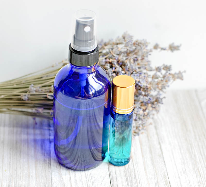 spray bottle next to roller ball of essential oils