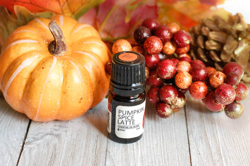 A group of fruit sitting on top of a wooden table with a pumpkin spice latte essential oil in front