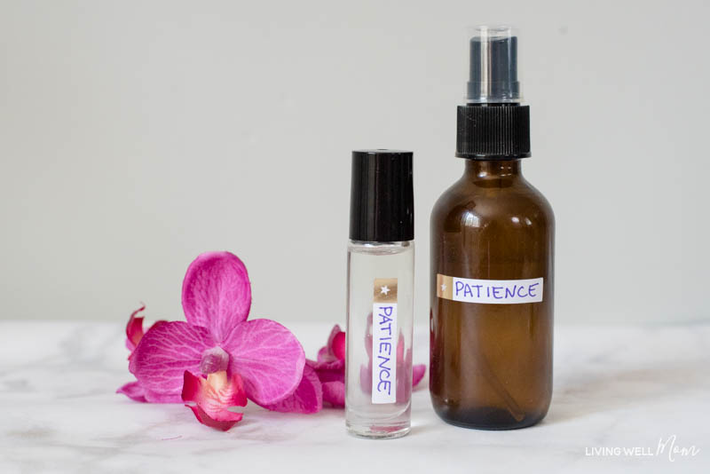 A glass spray bottle and roller bottle filled with DIY essential oil blend for moms.