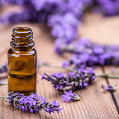 bottle of lavender essential oil and flowers on wood