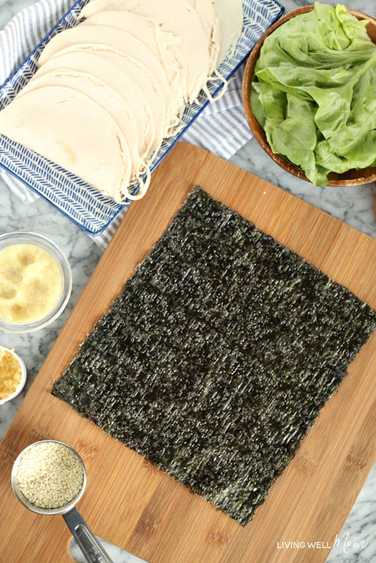 A bowl of food on a wooden cutting board, with dry seaweed and Sesame