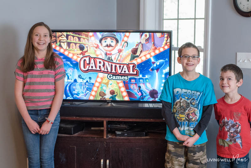 a boy and a girl standing in front of a tv with a Nintendo Switch Carnival game on it
