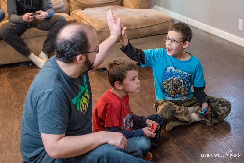 a father and a son high-fiving over a boy concentrating on a game