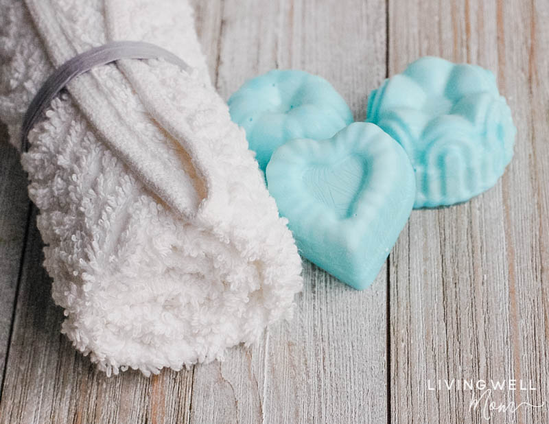 rolled white towel with blue heart shaped essential oil shower melts