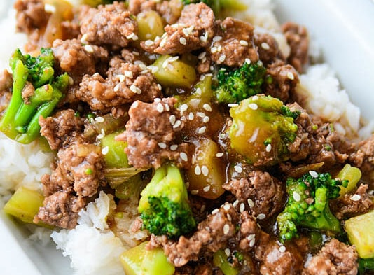 broccoli with ground beef and rice on a white plate