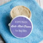 homemade anti-itch cream for bug bites with purple label container on blue towel