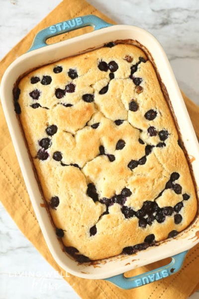 Freshly baked blueberry cake with fresh berries in a white baking dish.