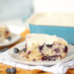 a piece of blueberry dump cake with cream icing on a plate
