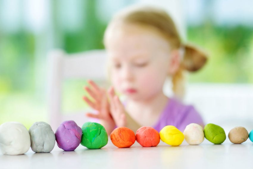 little girl playing with colorful playdough balls