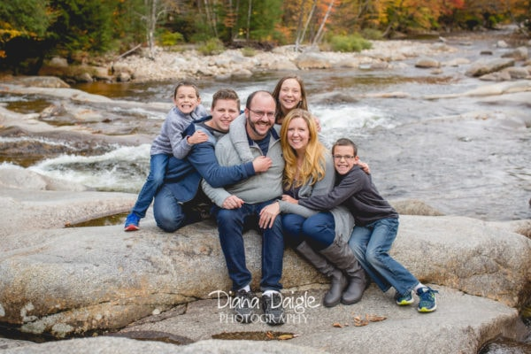 the Bragdon Family posing for a picture on some rocks in a river