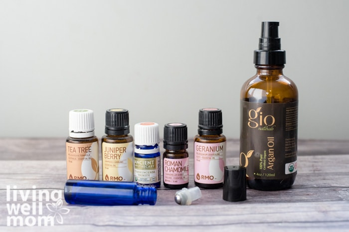 essential oil bottles, argan oil, and roller bottle on table