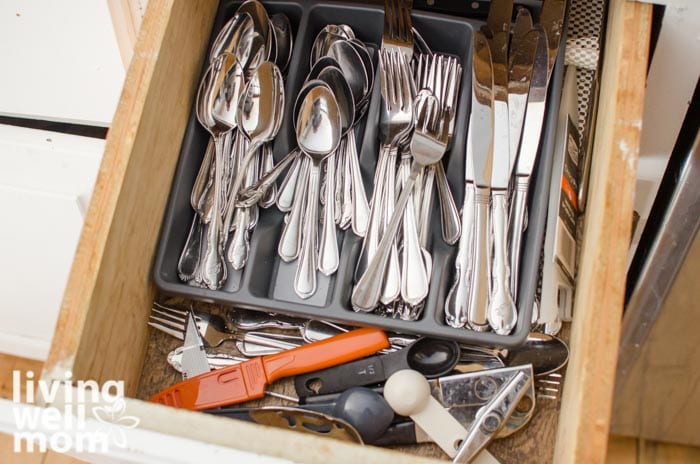 a disorganized drawer in a small kitchen