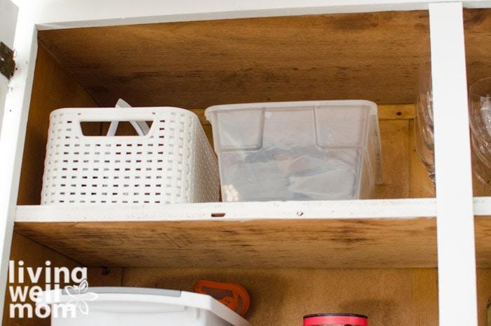 organized bins on a shelf of a kitchen cabinet