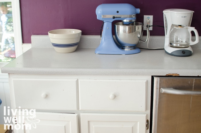 a kitchen countertop with a mixer, bowl and coffee maker on top.