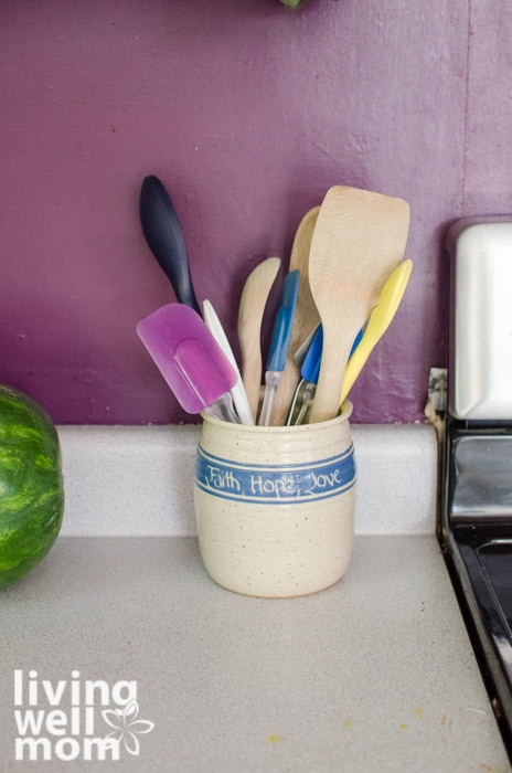 A canister sitting on a kitchen cabinet holding wooden and plastic spoons