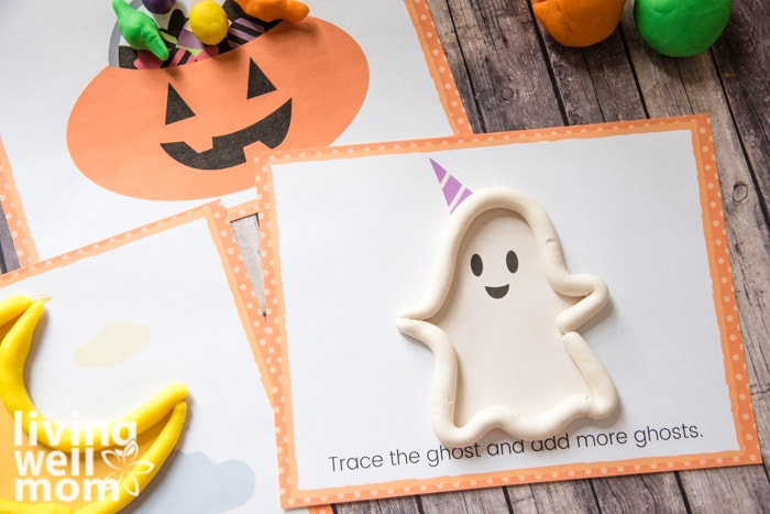 white playdough used to trace the image of a ghost for a Halloween kids activity