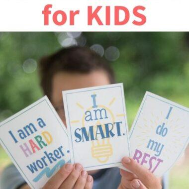 child holding up affirmation cards