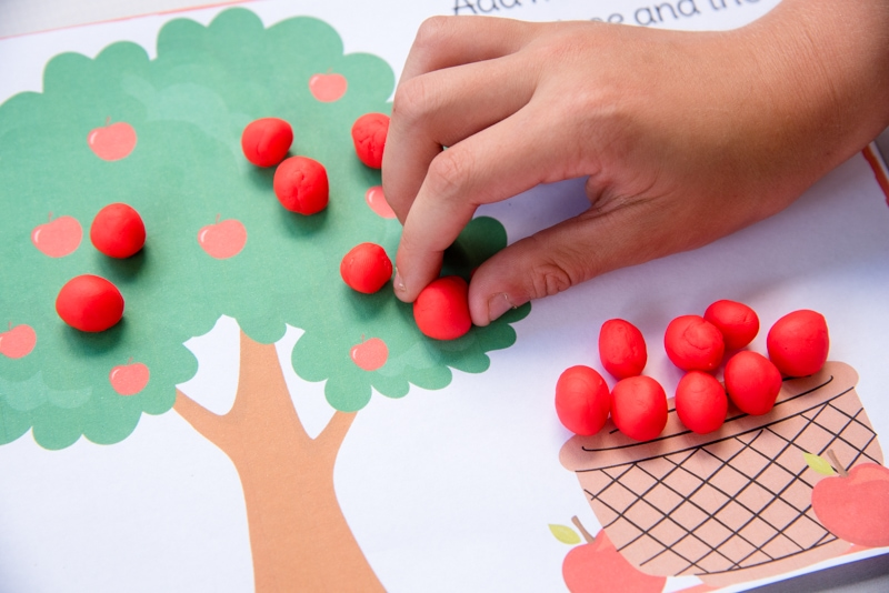 child playing with colorful apple tree seasons play dough mat