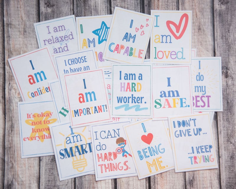 printed affirmations cards for children laid out on a wooden surface