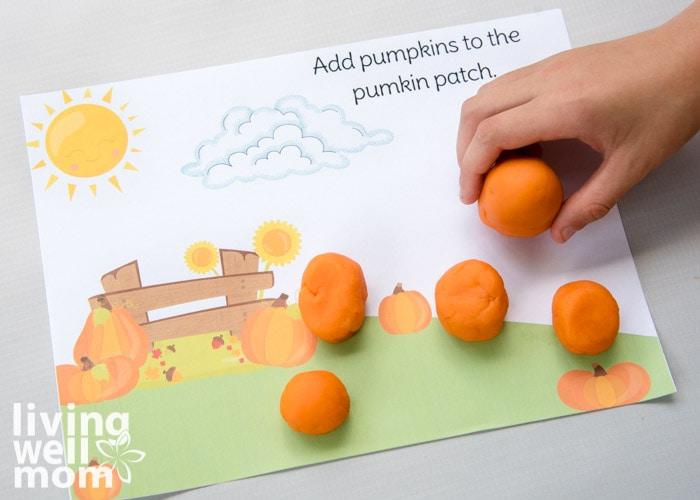 orange balls of playdough being added as pumpkins on activity mat