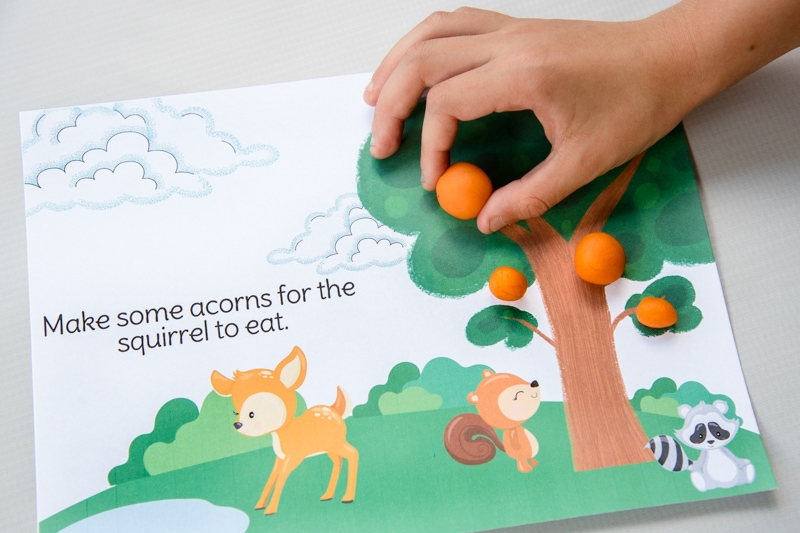 child hand playing with colorful spring animals play dough mat