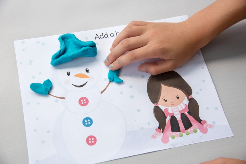 child's hand playing with snowman season winter play doh mat