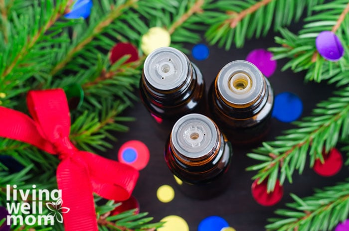 top view of three opened essential oil bottles in the midst of christmas greenery