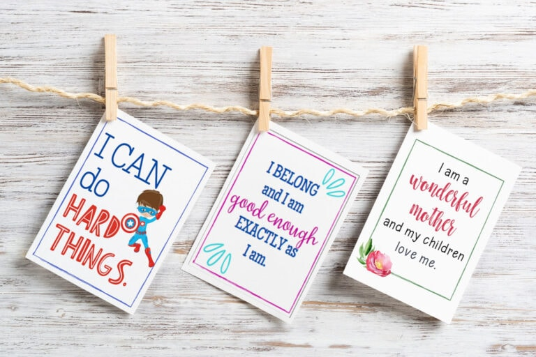 colorful positive affirmation cards for families hanging from clothespins on light wood background