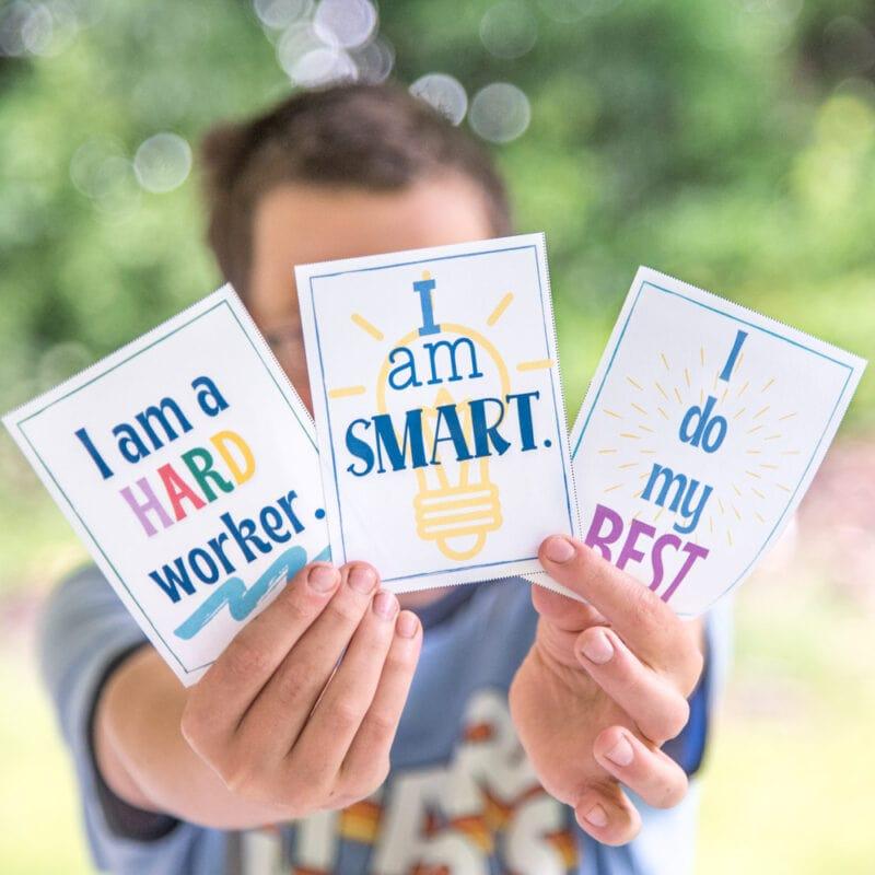 boy holding positive affirmation cards