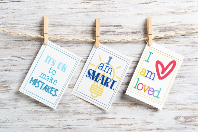 positive affirmation cards for children hanging from clothespins on wood background
