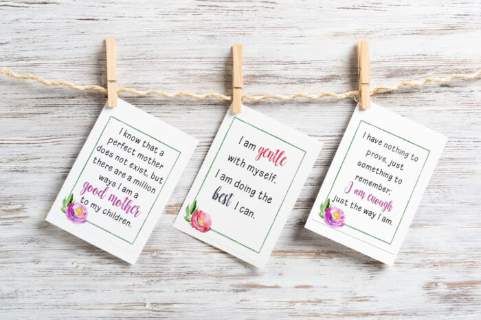 positive affirmation cards for mothers hanging from clothespins on wood background
