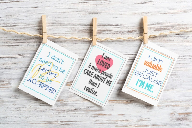 positive affirmation cards for teens hanging from clothespins on wood background