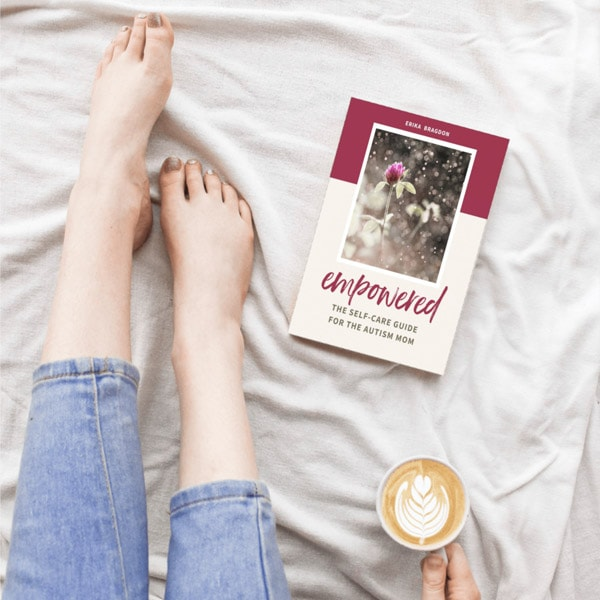 A woman sitting on a bed with a cup of coffee and a book for moms with autistic children