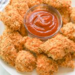 crispy healthy chicken nuggets on white plate with ketchup dipping sauce