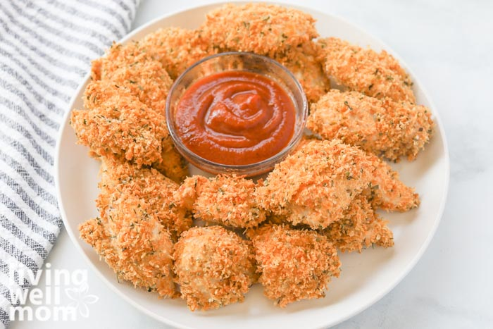 crispy chicken nuggets on a white plate with container of dipping sauce