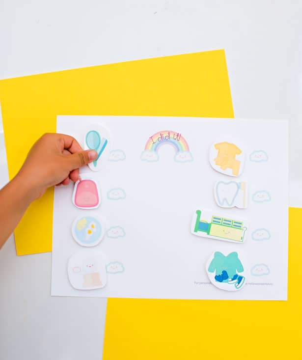 adding stickers to colorful yellow chore chart for kids