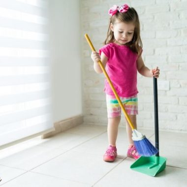 A little girl sweeping a white floor