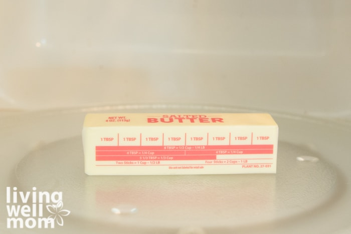 A stick of butter, still in the wrapper, on the tray inside of a microwave.