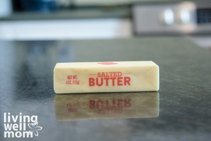 A softened stick of salted butter on a dark countertop.