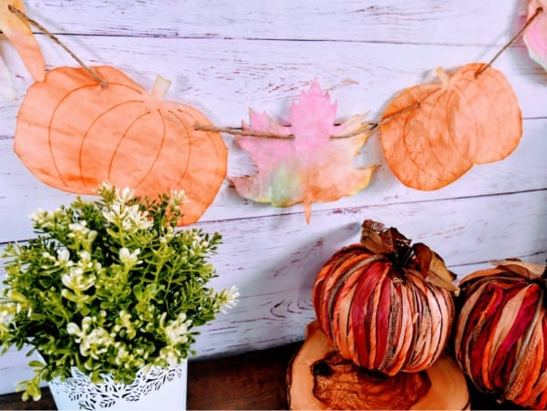 garland with painted pumpkins and leaves made from coffee filters